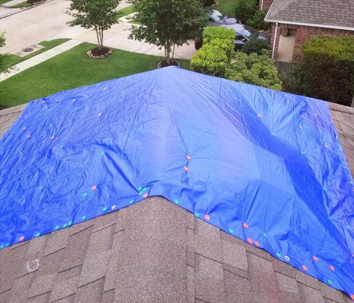 Blue tarp on roof. Roof tarp service